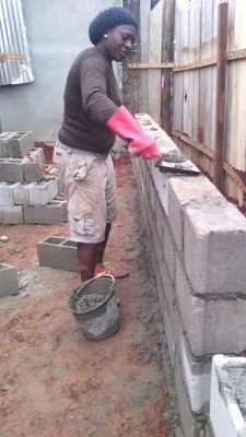 Dignity in labour: Woman seen building a fence